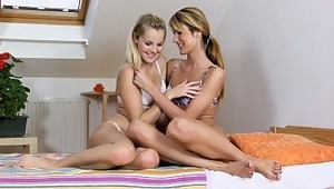 Sally and Kandy - Steamy blondes Kandy, purple undies, and Sally, white bra and panties, playfully chat and embrace in a small bed, then start to lovingly kiss each other. They takes off their bras, fondle and suck each other's firm tits, then slip o