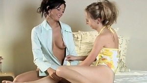 Anastasia and Emily - Enchanting teens Anastasia, black hair, and Emily, blonde, embrace and kiss playfully in their dorm room bed, then take off their shirts to fondle and suck each other's firm tits and hard nipples. Emily massages Anastasia's
