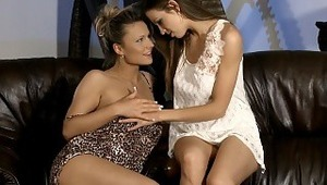 Juliette and Jolie - Dazzling brunette Juliette in white dress and her gorgeous friend Jolie look each other deeply in the eyes and make out passionately on a couple of leather armchairs in the living room, then Juliette pulls down Jolie's animal pr