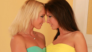 Kissy and Caty - Luscious vixens Caty, blonde, and Kissy, brown hair, kiss and caress passionately in the living room, pull down the tops of their dresses, then fondle and suck one another's firm tits. They take off their dresses and panties, Caty sp