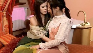 Caprice and Krissy - stunning brunette Caprice in green dress and lovely teenie Krissy embrace and kiss tenderly on a divan in the bathroom, then they pull down their dresses to fondle and lick one anothers' firm boobs. They help each other off with