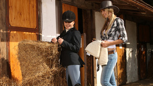 Aneta and Mya - Luscious cowgirl Aneta helps adorable Mya, dressed in an English riding outfit, off of her horse and they share a passionate kiss and a loving embrace. They strip off their clothes, make out and suck each other's firm tits against a b