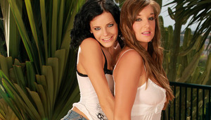 Cate and Adela - Dark haired hottie Adela and brunette cutie Cate make out passionately on a large pillow in the garden, then they strip off their tops to lick and fondle one anothers' ample breasts. Adela pulls off Cate's denim mini and white p