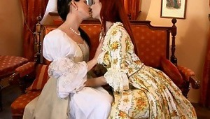 Faith and Waleria - Sultry redhead Faith and raven haired siren Waleria caress and make out passionately on an antique sofa indoors, then Faith helps Waleria off with her Victorian dress to fondle her ample breasts and erect nipples. Faith goes down on Wa