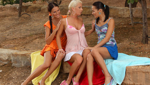 Iris, Deny and Devin - Bewitching brunettes Deny, in orange, and Devin are sitting in the garden on a blanket with sultry blonde Iris between them. They make out lustily and pull down their dresses and take off their bras, then they knead and blow each ot