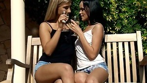 Angellina and Nadija - petite stunner Angellina and blondie sweetie Nadija toast with juice on a wooden bench on the patio, then embrace and kiss tenderly. They strip off their tops to suck and fondle one anothers' beautiful, firm breasts, then pull