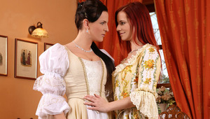 Faith and Waleria - Sultry redhead Faith and raven haired siren Waleria caress and make out passionately on an antique sofa indoors, then Faith helps Waleria off with her Victorian dress to fondle her ample titties and erect nipples. Faith goes down on Wa