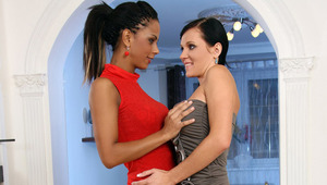 Izabella and Ema - Ema and Izabella (red dress) are kissing in the living room.  They lick and blow each others nipples, and undress each other.  Then they lie on the couch and Ema inserts two fingers into Izabella's ass hole and starts eating her pu