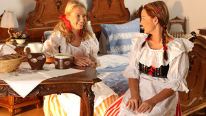 Judit and Jessica - Adorable blonde Jessica and lovely teen Judit are eating bread in the kitchen wearing striped, antique dresses with puffy, white bustiers. Judie breaks a slice of bread and they taste each other's slices, then they get up and site